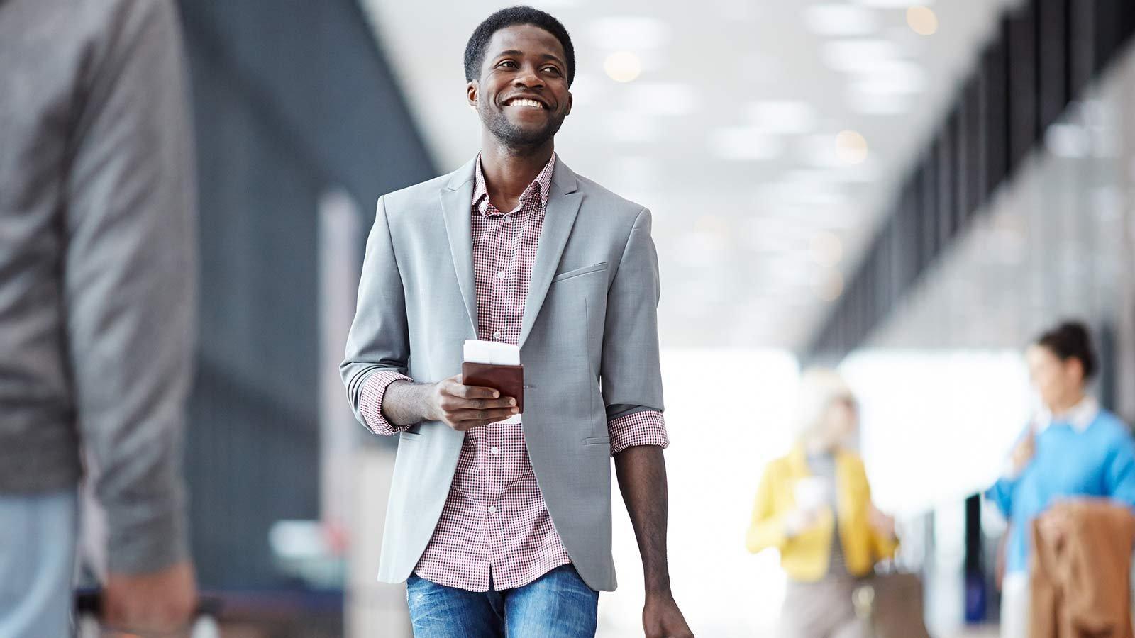 Man walking through airport holding passport