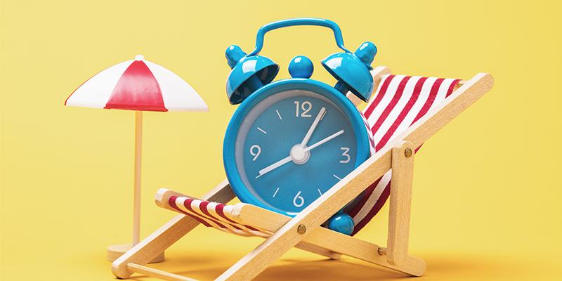 antique alarm clock sitting in beach chair next to a beach umbrella