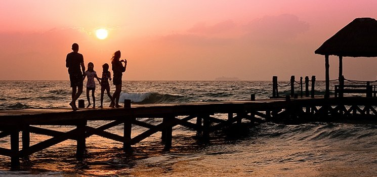 Family standing on dock at sunset