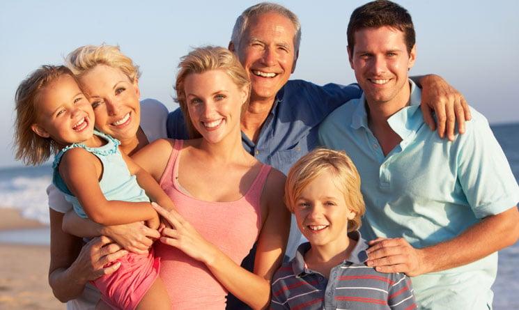 Multigenerational family posing for photo on beach