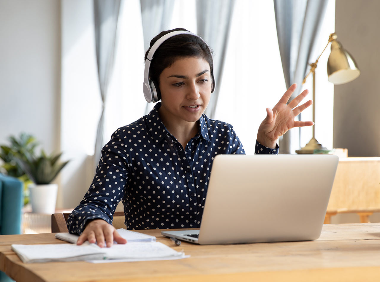 Young female advisor wearing headphones and speaking to her client during a video chat