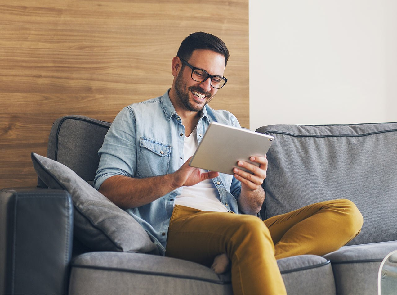 Smiling man sitting on couch and communicating with advisor on a tablet