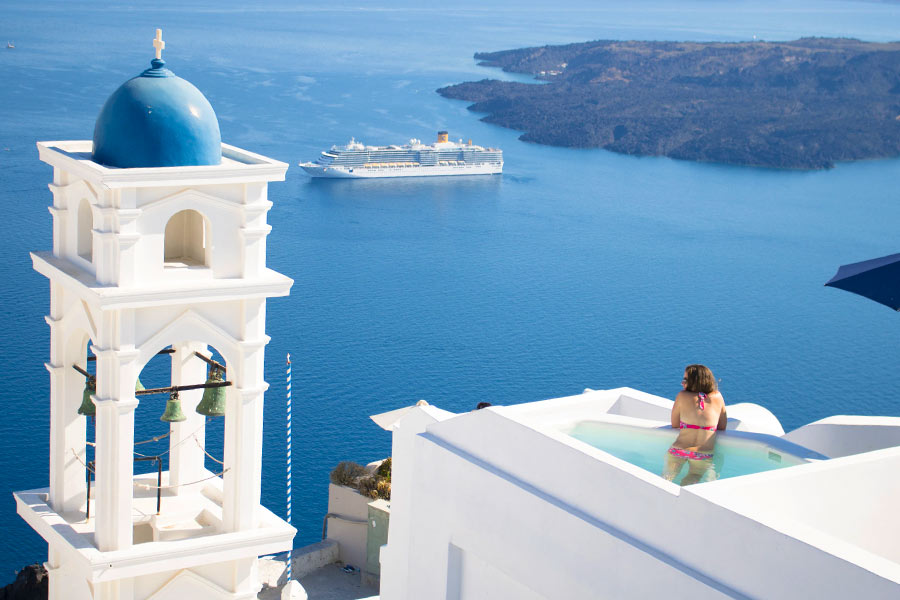 Woman in rooftop pool overlooking ocean in Greece
